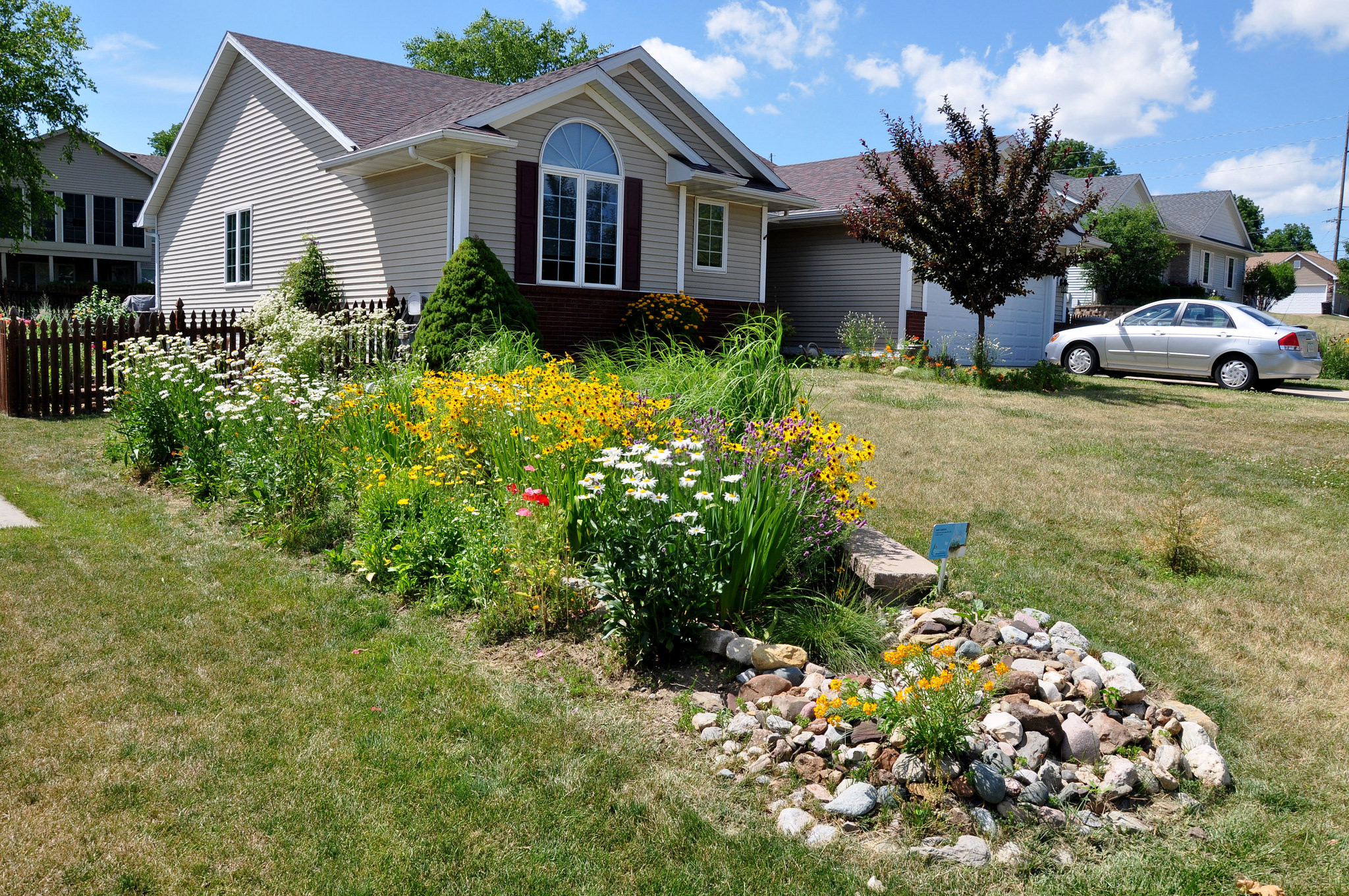 Raingarden in lawn in front of newer home. Rock mulch.