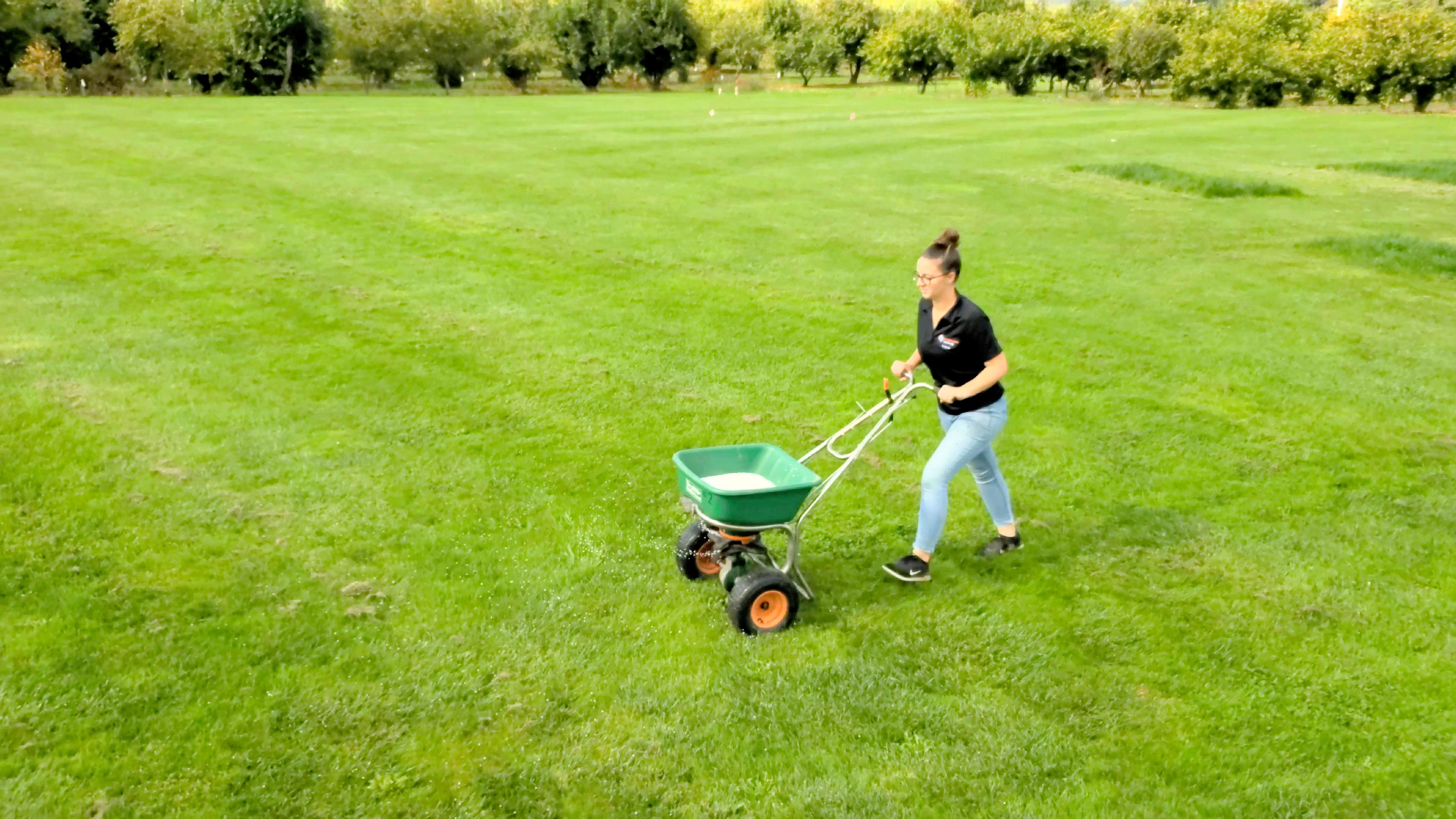 Woman pushing a fertilizer spreader across a field