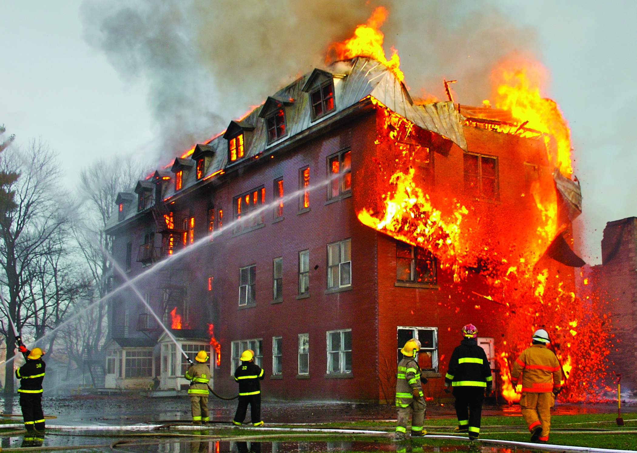 Figure 11. A major fire engulfs an urban structure despite efforts by firefighters to extinguish it.