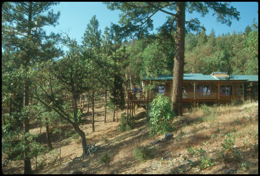 Figure 4. This home is in the forest, but the surrounding land has been treated to remove fuels and create defensible space.