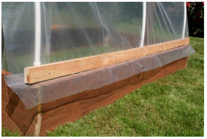 Secure the side curtain plastic with two D boards that sandwich the plastic and rest on top of the raised bed.