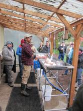 Poultry processing demonstration. Covered area with tables and sinks.