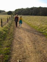A woman walks down a dirt road with a young girl
