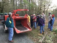 A group of landowners standing around a chipper
