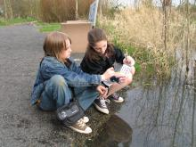 Two middle school students collect and analyze water samples from a stream.